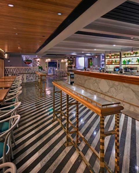 Dramatic striped floor tiles in front of bar at The Ivanhoe Hotel by Paul Kelly Design