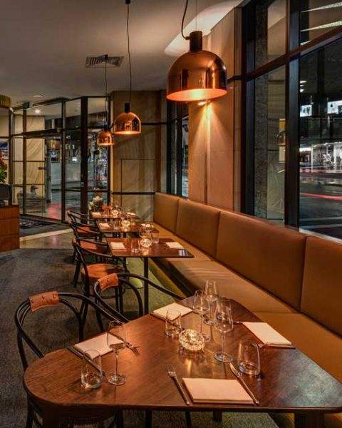 Close view of table arrangement with feature lighting at 2 Bond Street, design by Paul Kelly Design