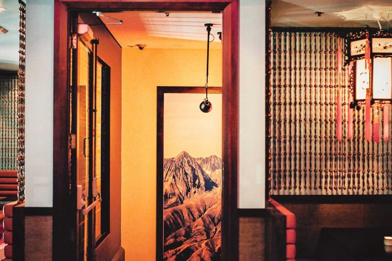 Wide photo of a room in the Smoking Panda showing a painting in the stairwell and a lighting fixture