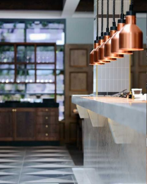 Copper pendant lights over a service area at The Workshop, design by Paul Kelly Design