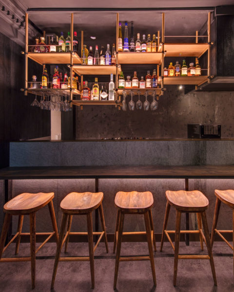 View of the Kenny Rens bar timber dowel shelving and bottle display, interior by Paul Kelly Design