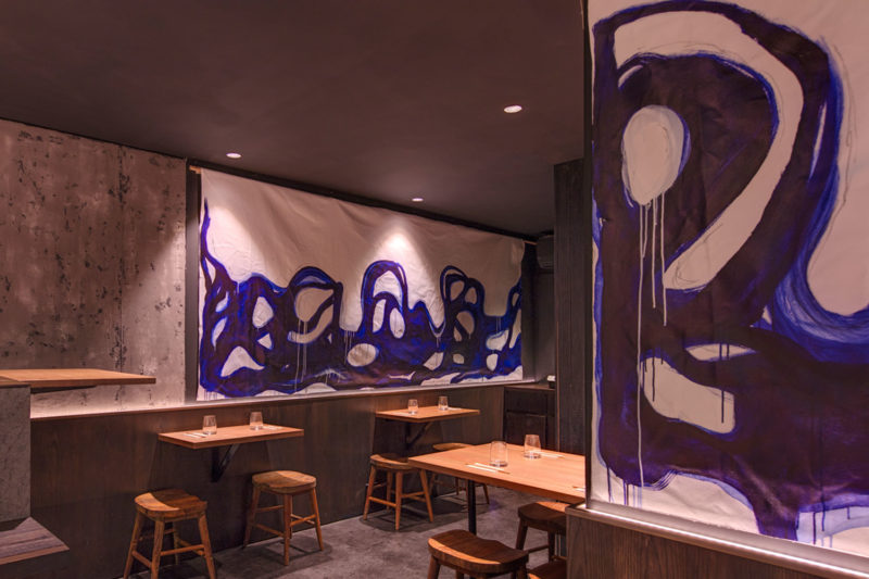 View of the Kenny Rens dining area, timber seats and bold blue brush stroked artwork, interior by Paul Kelly Design